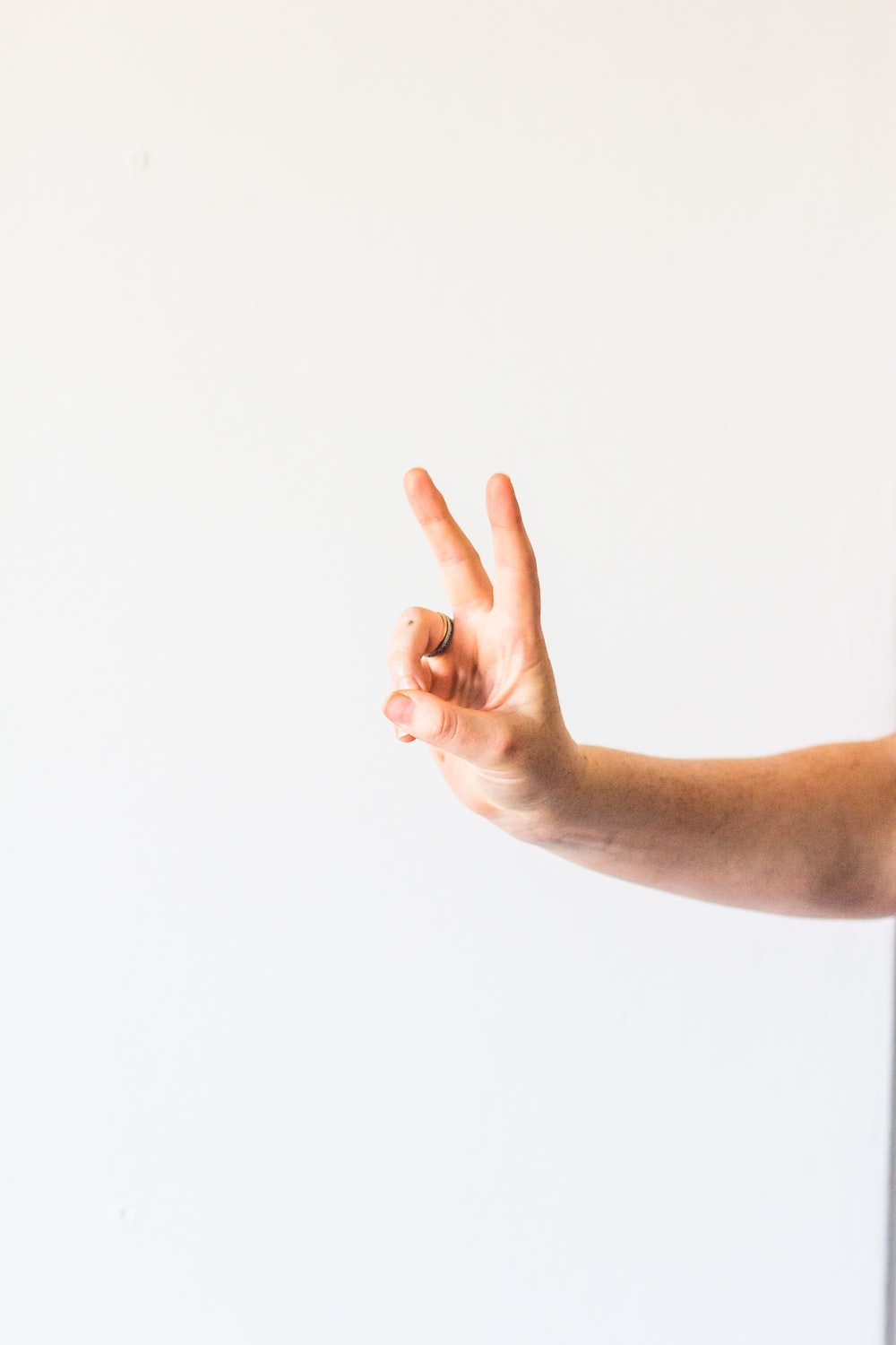 persons left hand doing thumbs up sign
