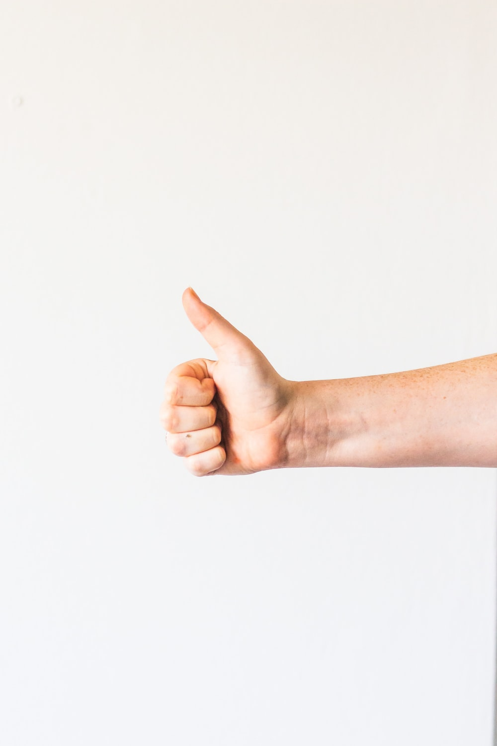 persons right hand doing thumbs up