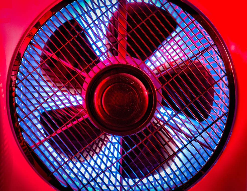 black and gray fan on brown wooden table