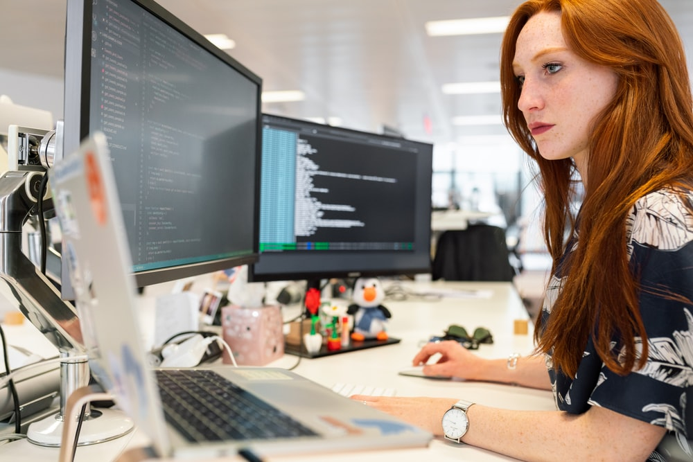woman in green shirt sitting in front of computer