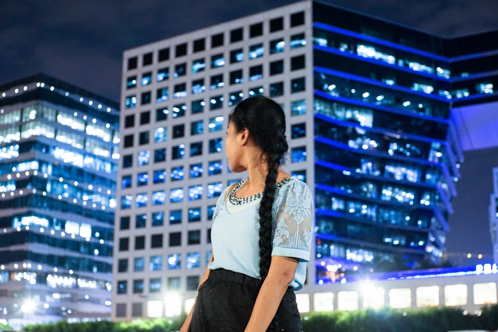 woman in white and black t-shirt standing near building during night time