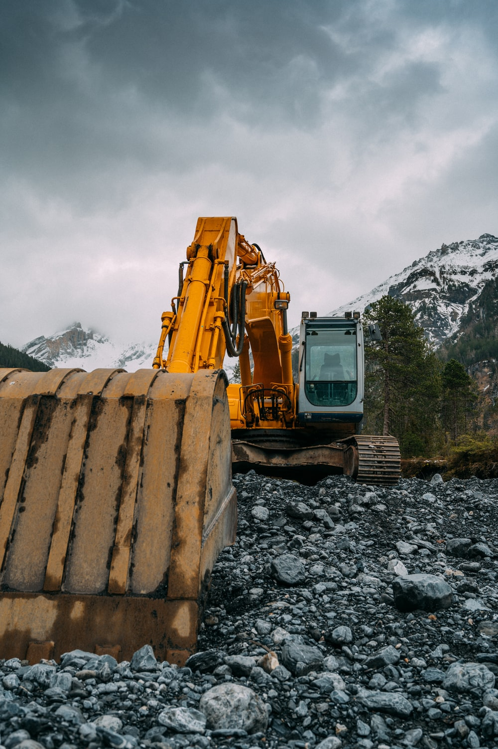 yellow and black heavy equipment on rocky ground