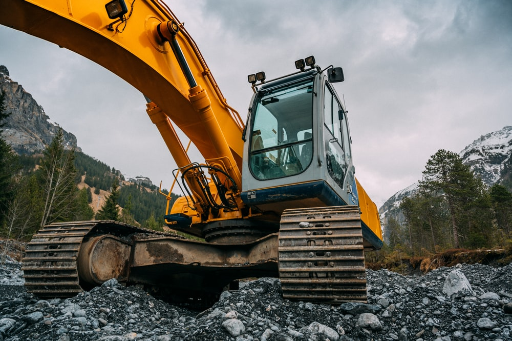 yellow and green excavator on rocky ground during daytime