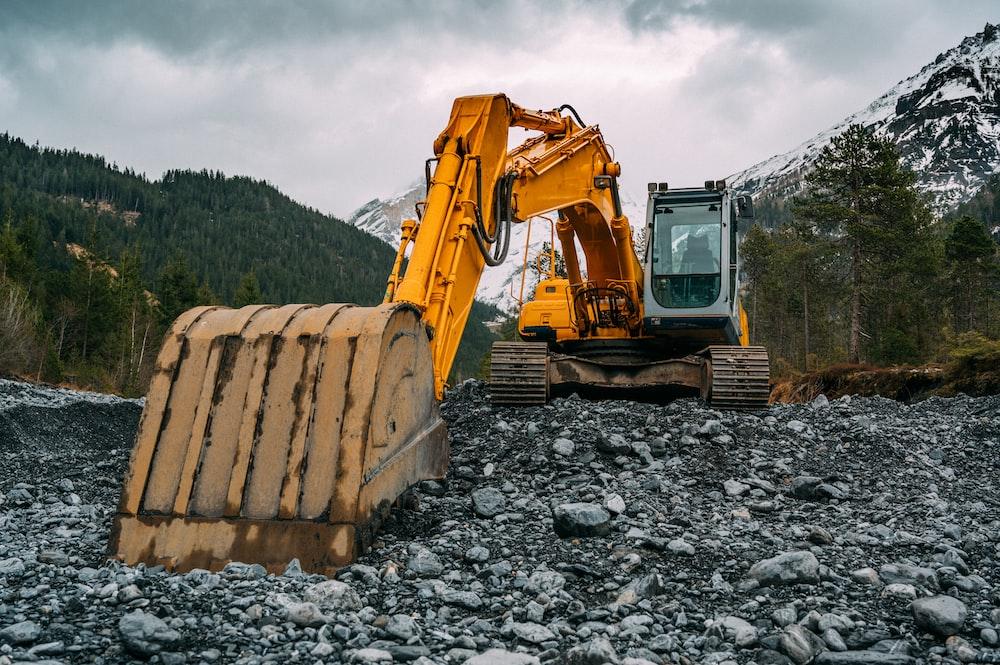 yellow and black excavator on rocky ground