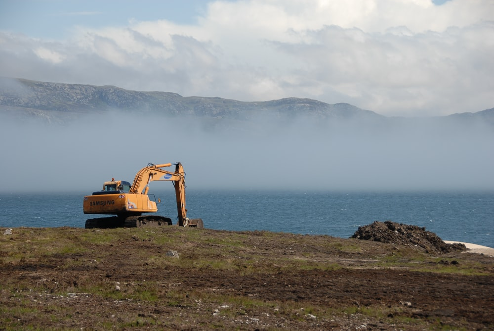 yellow and black heavy equipment near body of water during daytime