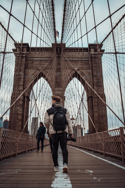 man in black jacket and black pants standing on brown bridge