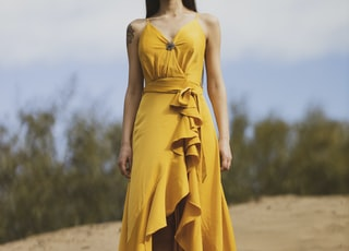 woman in yellow tube dress standing on brown sand during daytime