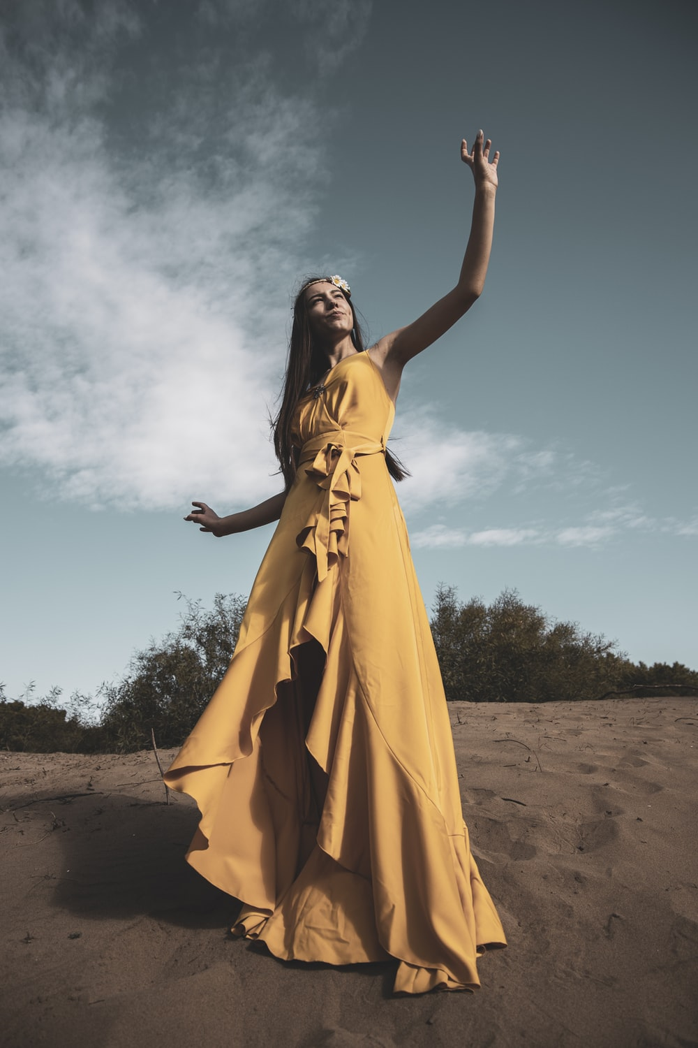 woman in yellow sleeveless dress standing on brown sand during daytime