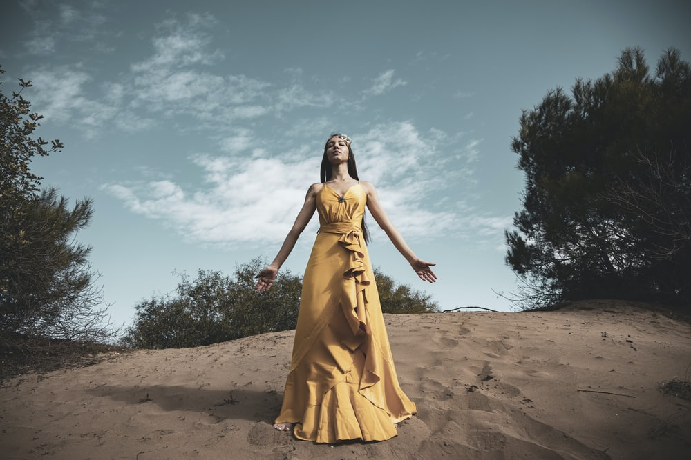 woman in yellow dress standing on brown sand under blue sky during daytime