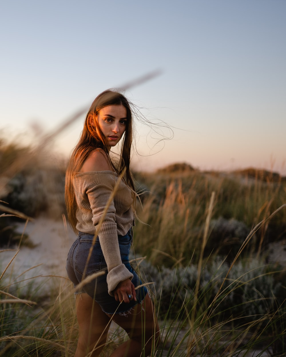 woman in brown long sleeve shirt and blue denim jeans standing on green grass field during