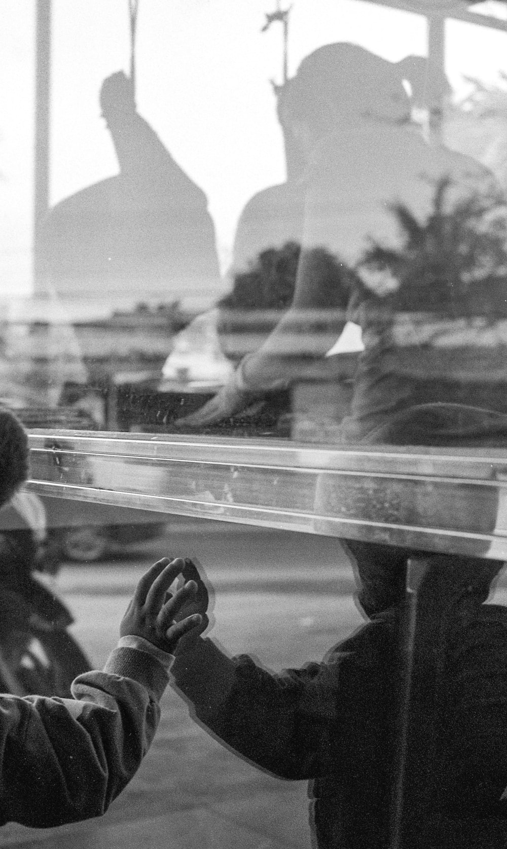 grayscale photo of people sitting on bench