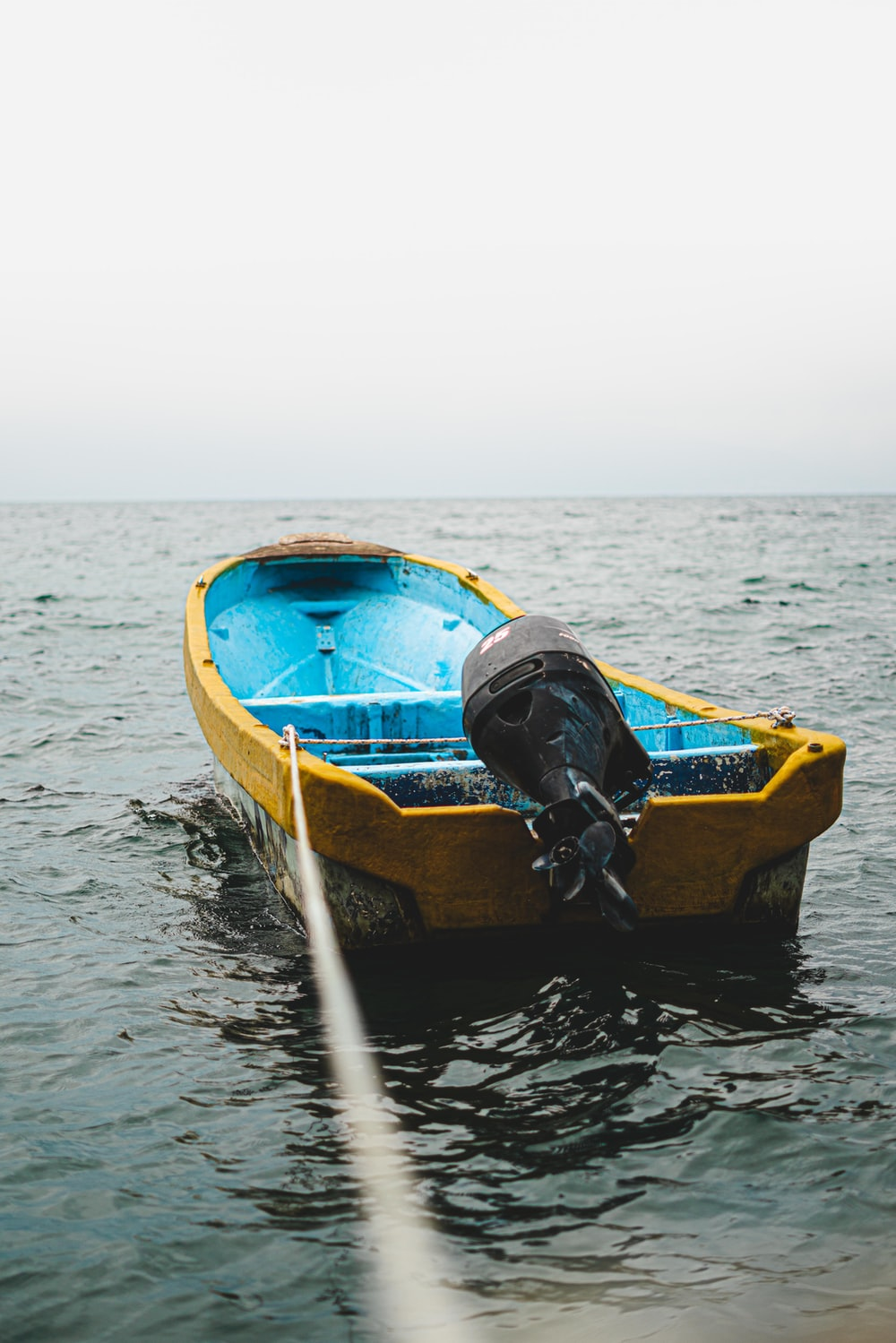 blue and yellow boat on water during daytime