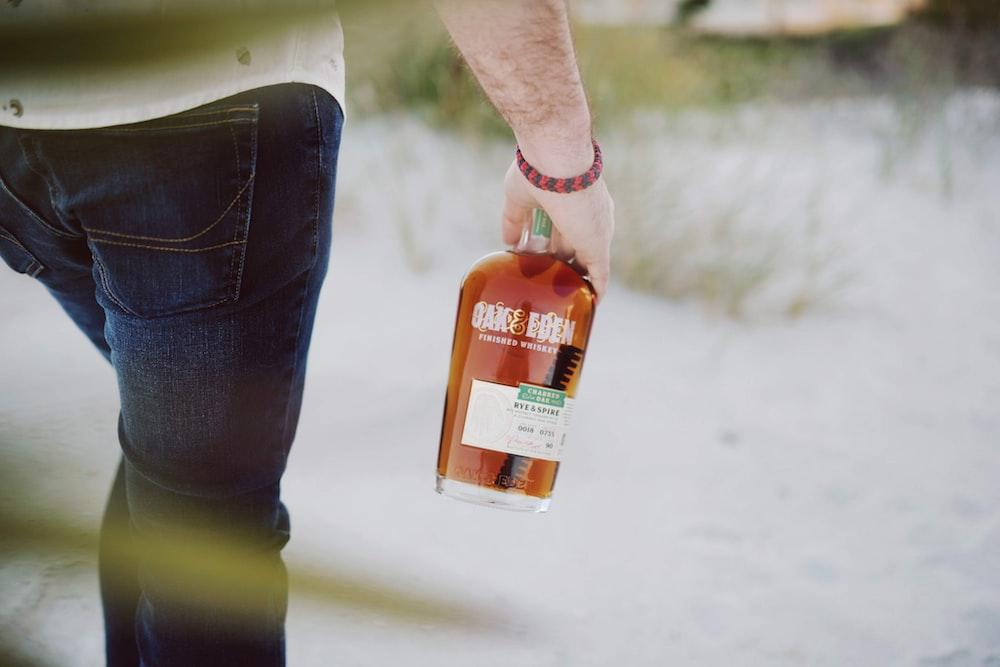 person holding orange plastic bottle