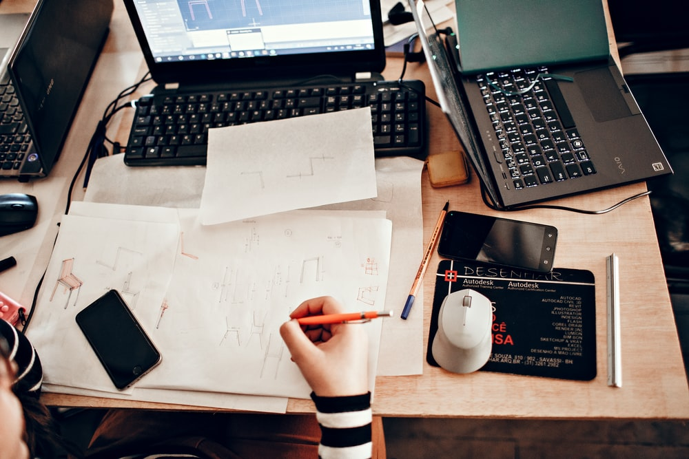 person holding white printer paper near black laptop computer