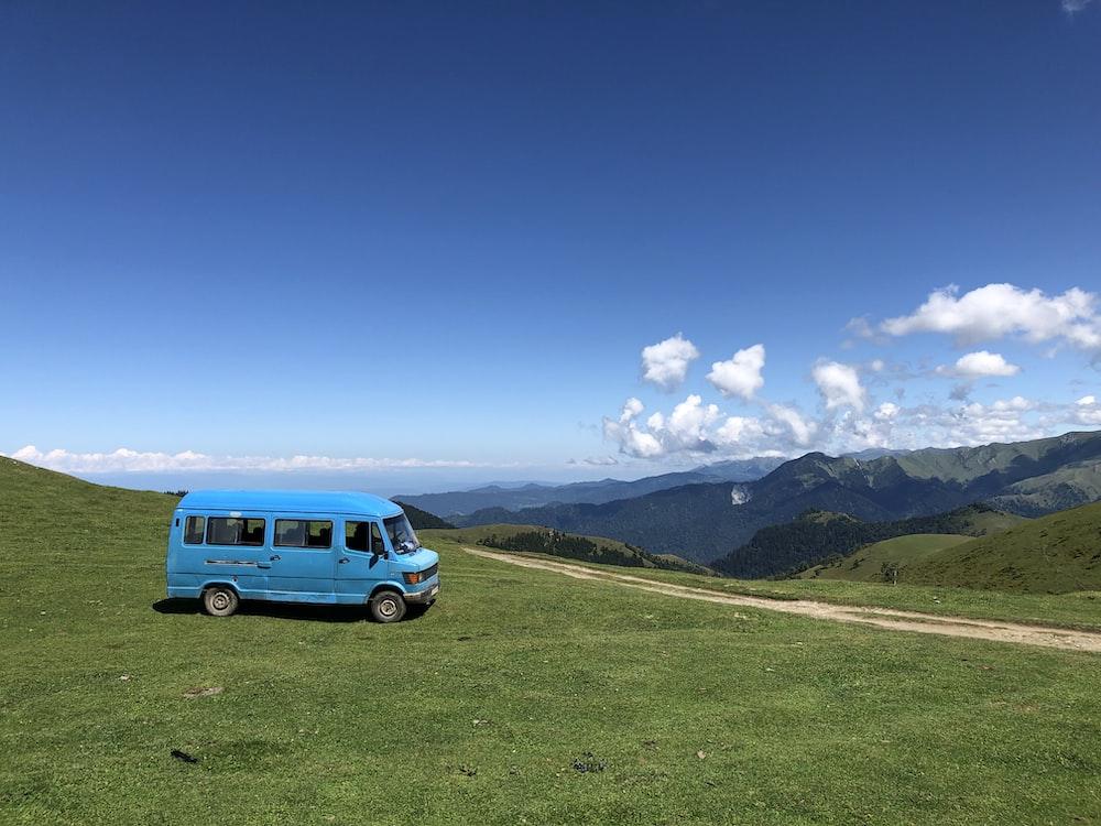 blue van on green grass field during daytime