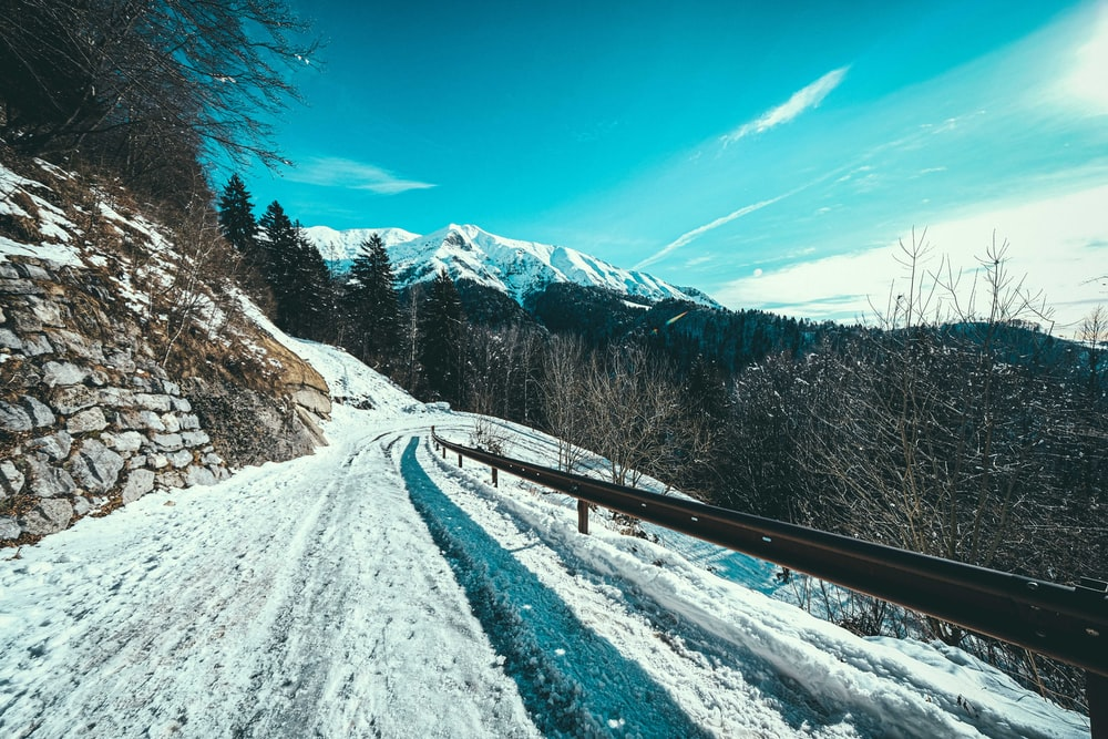 snow covered road near trees and mountains under blue sky during daytime
