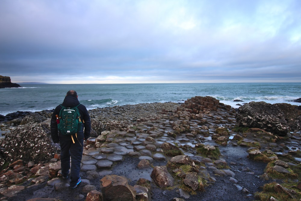 man in black jacket standing on rocky shore during daytime