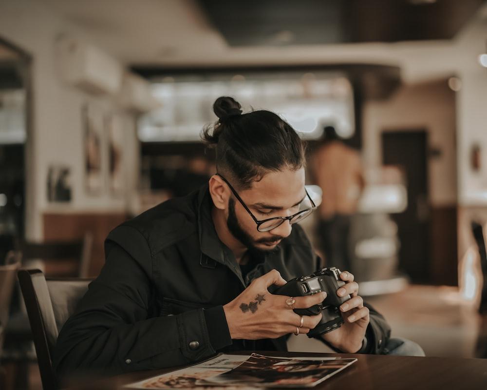 man in black jacket using smartphone