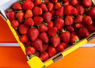 red strawberries on yellow plastic container