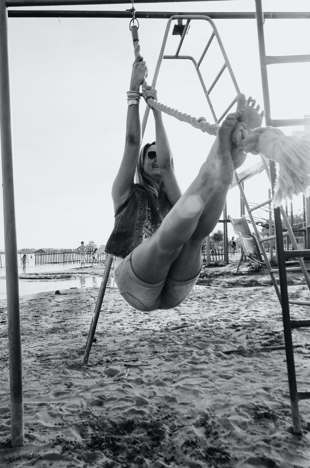grayscale photo of woman in black tank top and shorts hanging on white rope