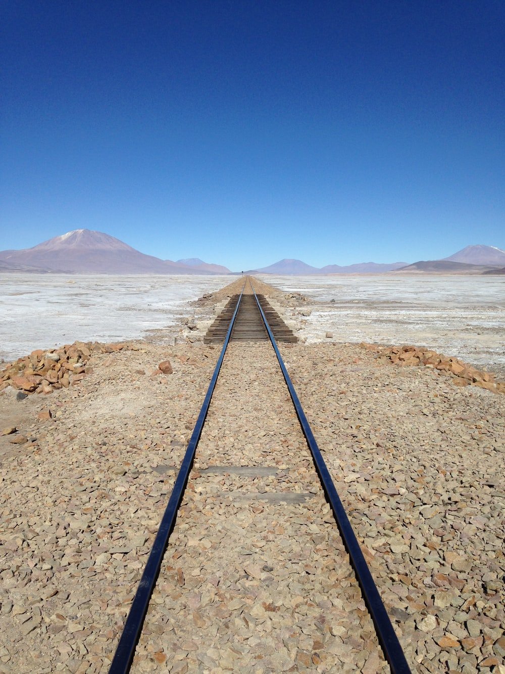 black metal train rail on brown rocky shore during daytime