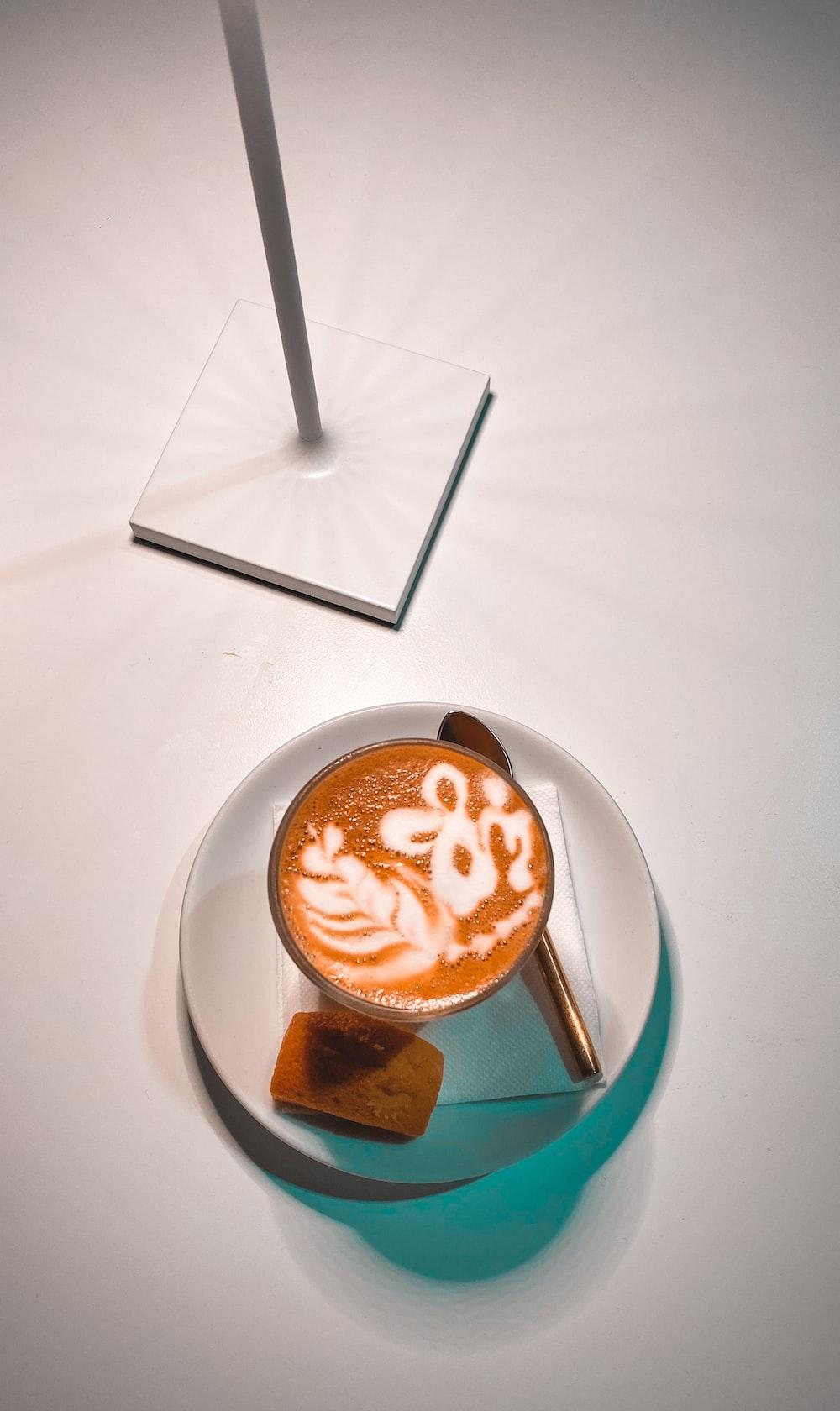 white ceramic mug with cappuccino on white ceramic saucer