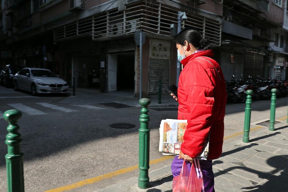man in red jacket and black pants walking on sidewalk during daytime