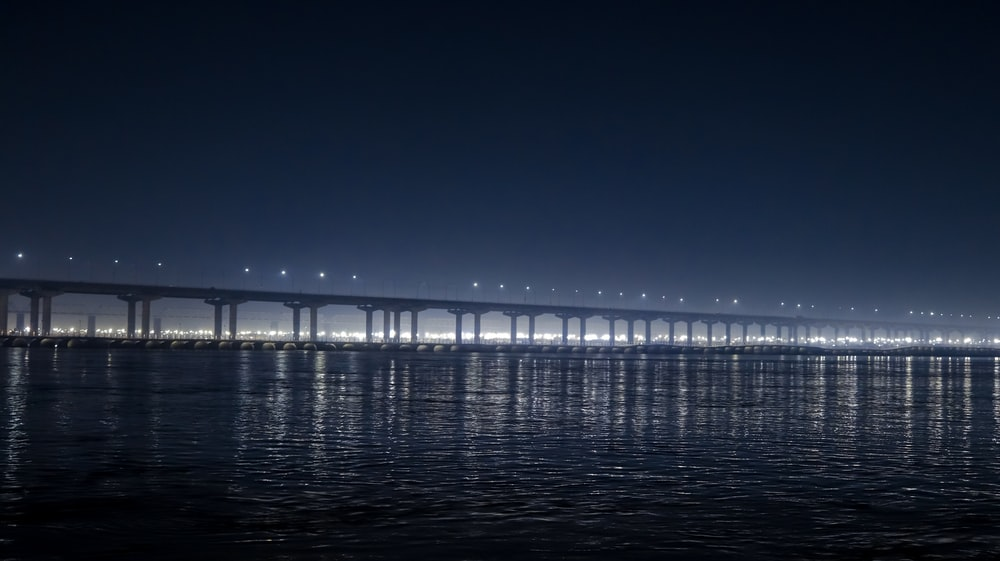 white bridge on body of water during night time