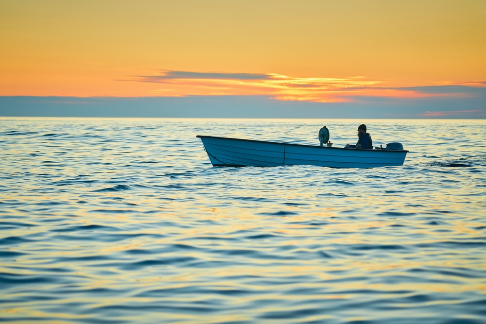 silhouette of 2 people riding on boat during sunset