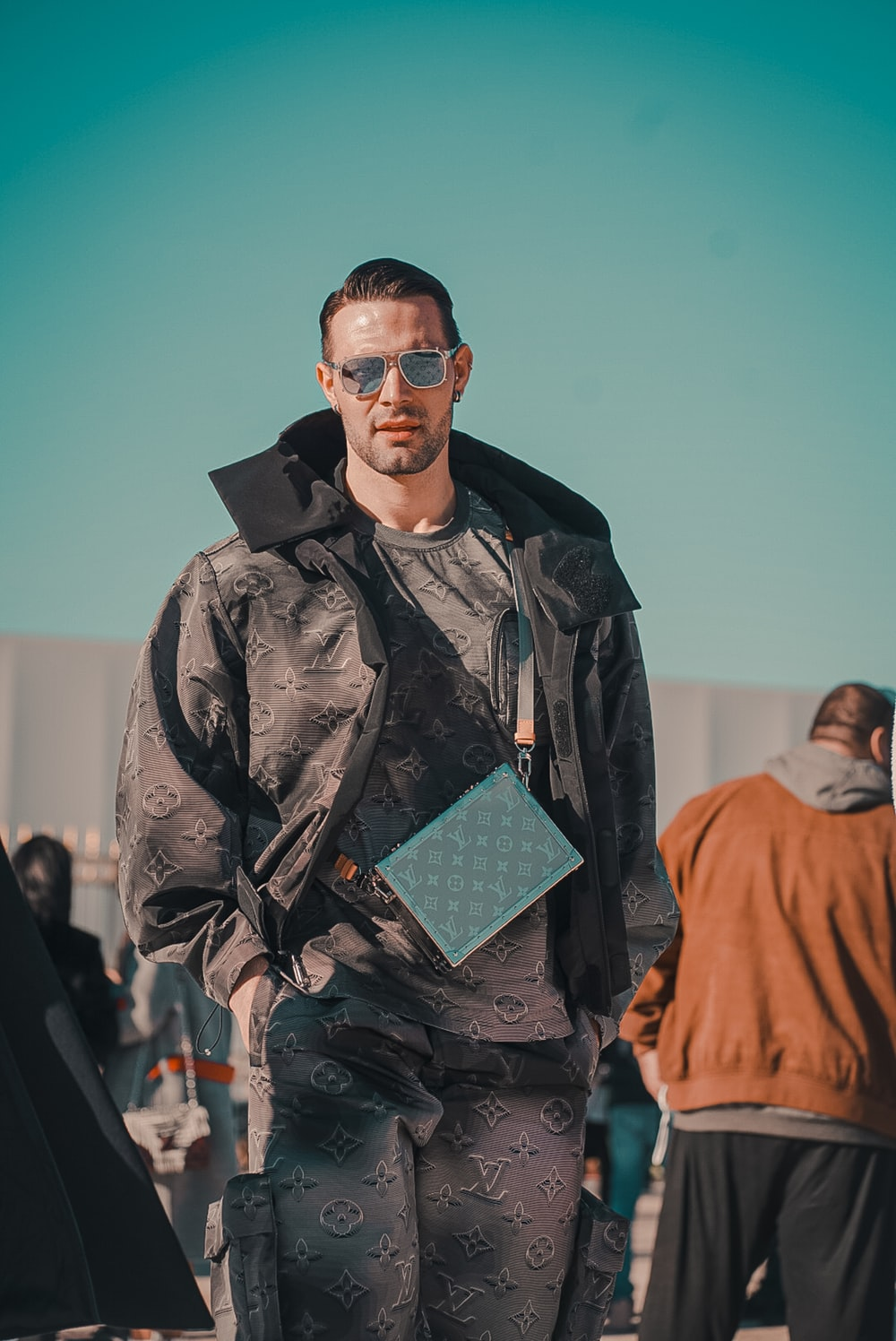 man in black sunglasses and black coat holding green book