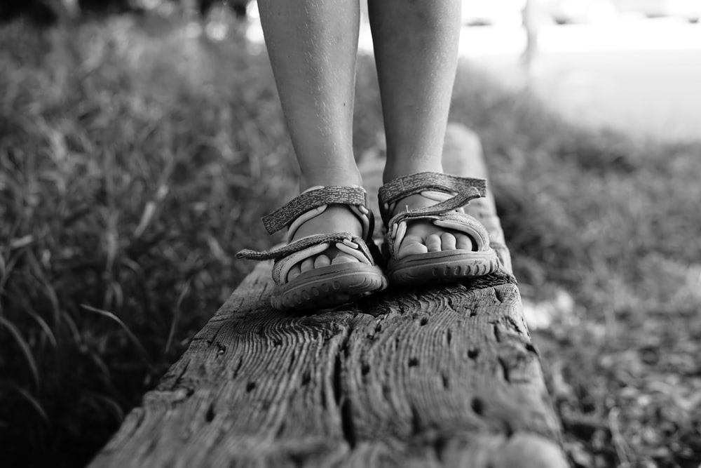 grayscale photo of person wearing sandals