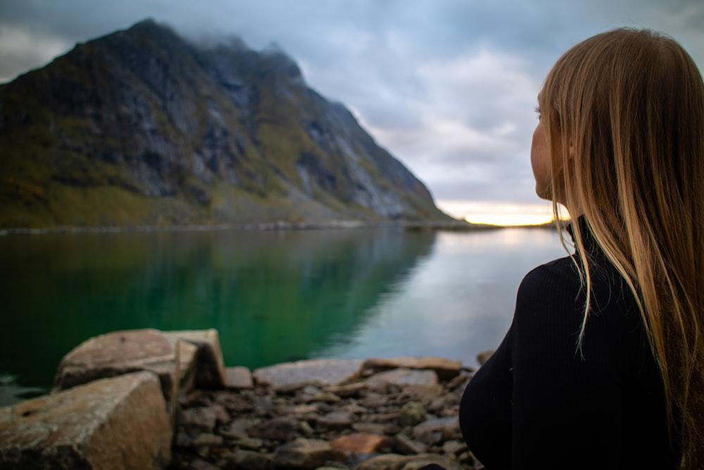 woman in black jacket sitting on rock near lake during daytime