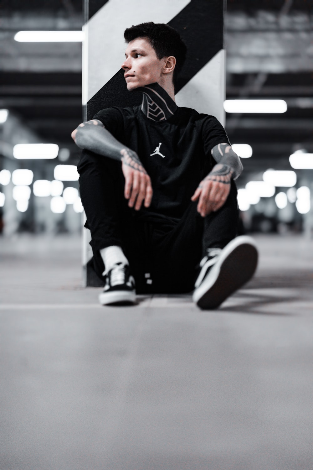 man in black and white nike sneakers sitting on floor