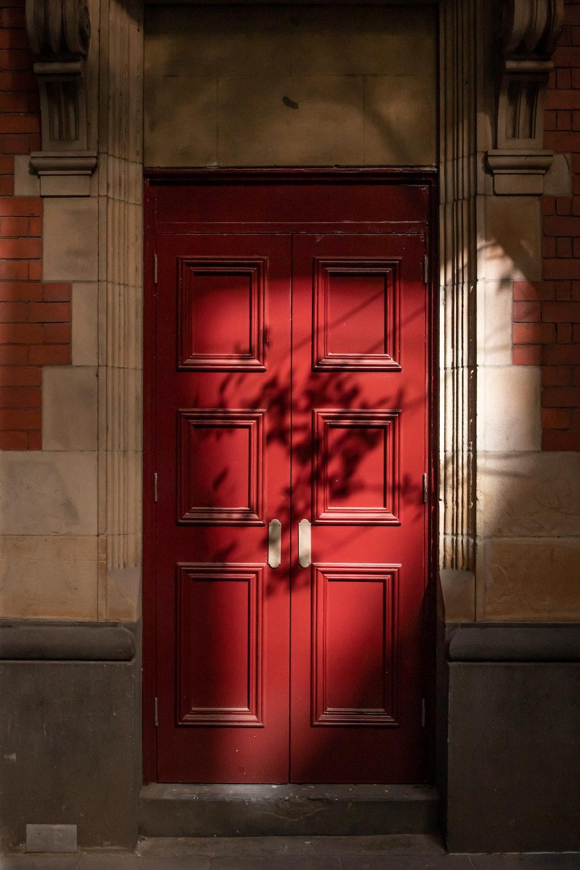 red wooden door on gray concrete wall