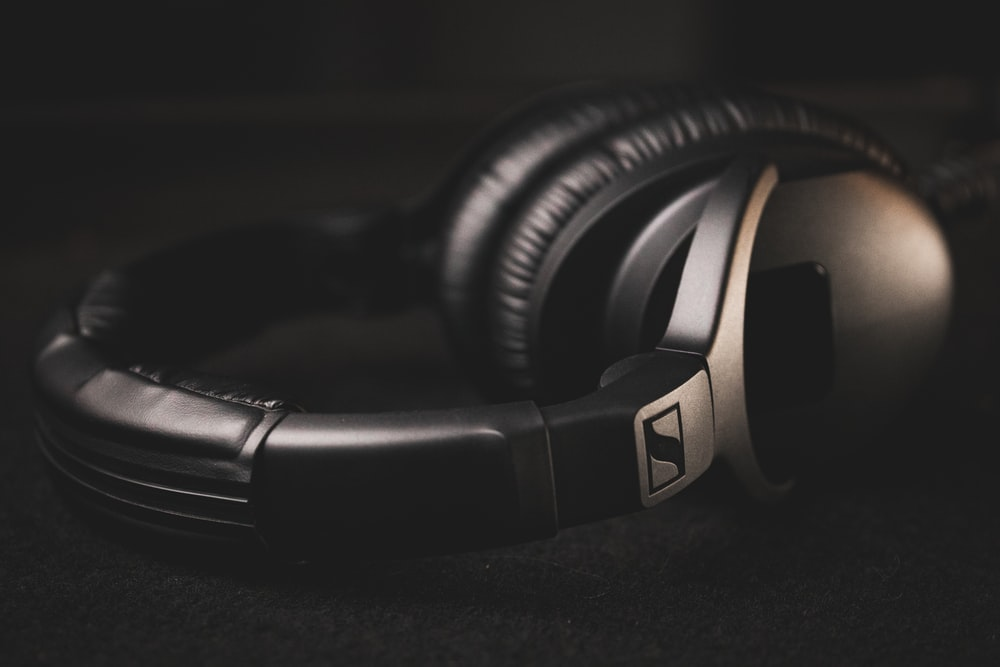 black and silver headphones on black textile