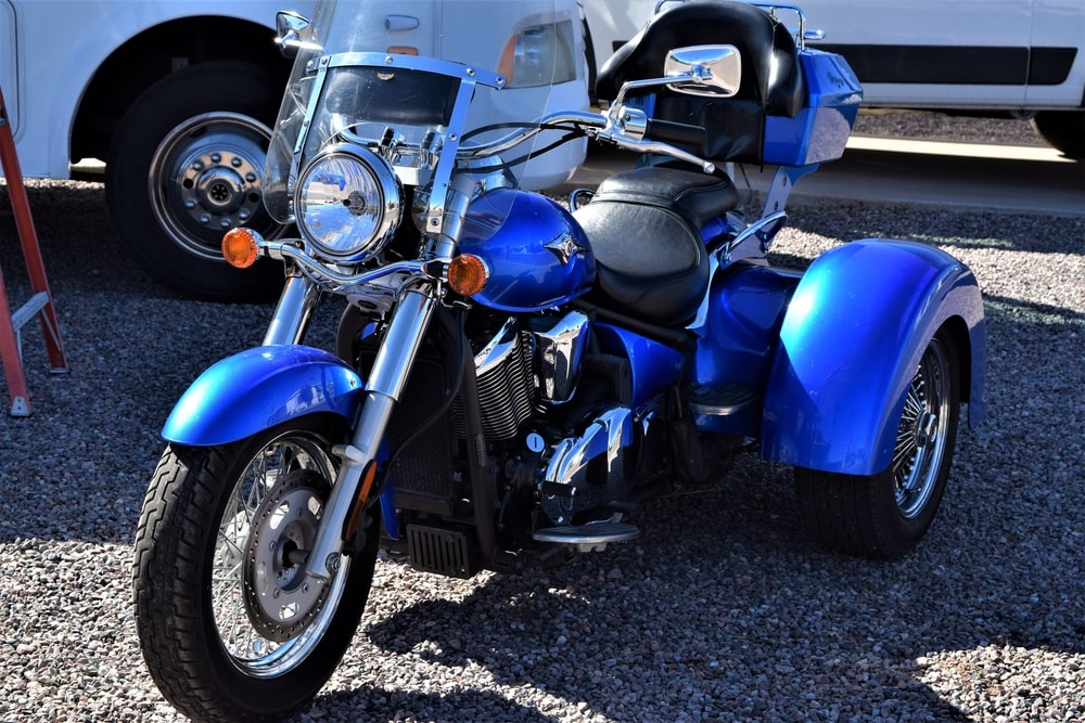 blue and black motorcycle on gray asphalt road during daytime