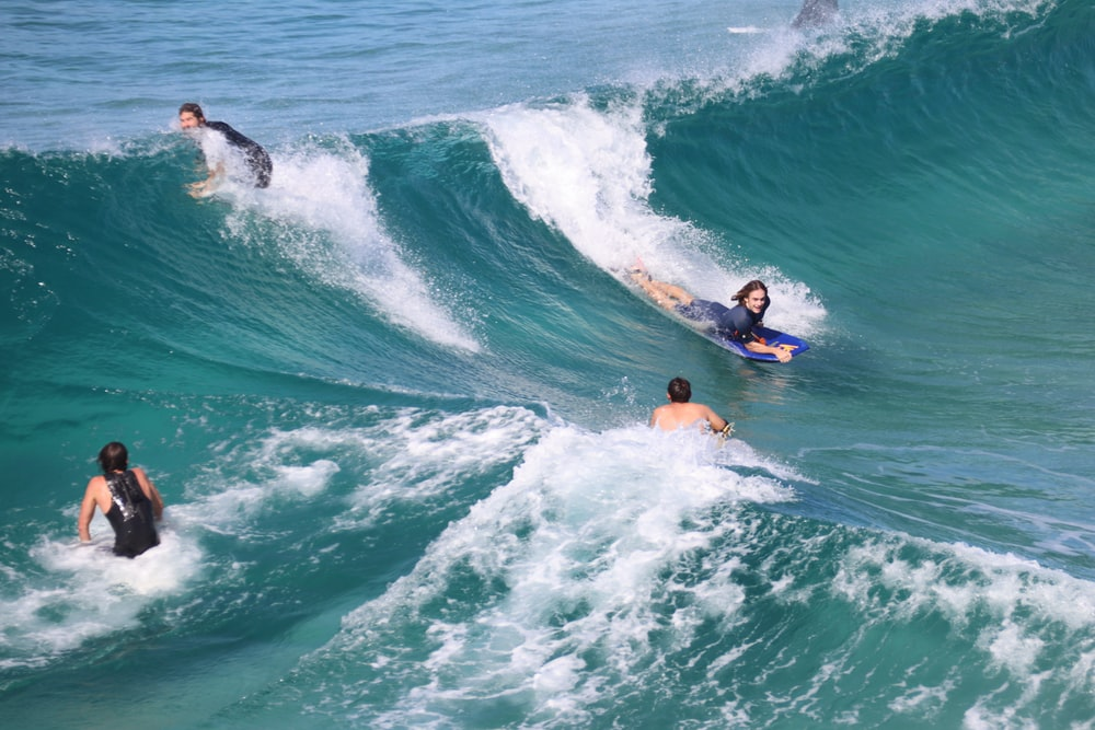 2 people surfing on sea during daytime