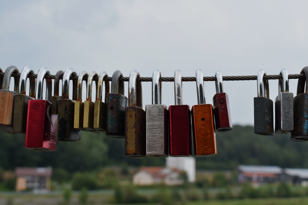 red and brown padlock on gray metal wire