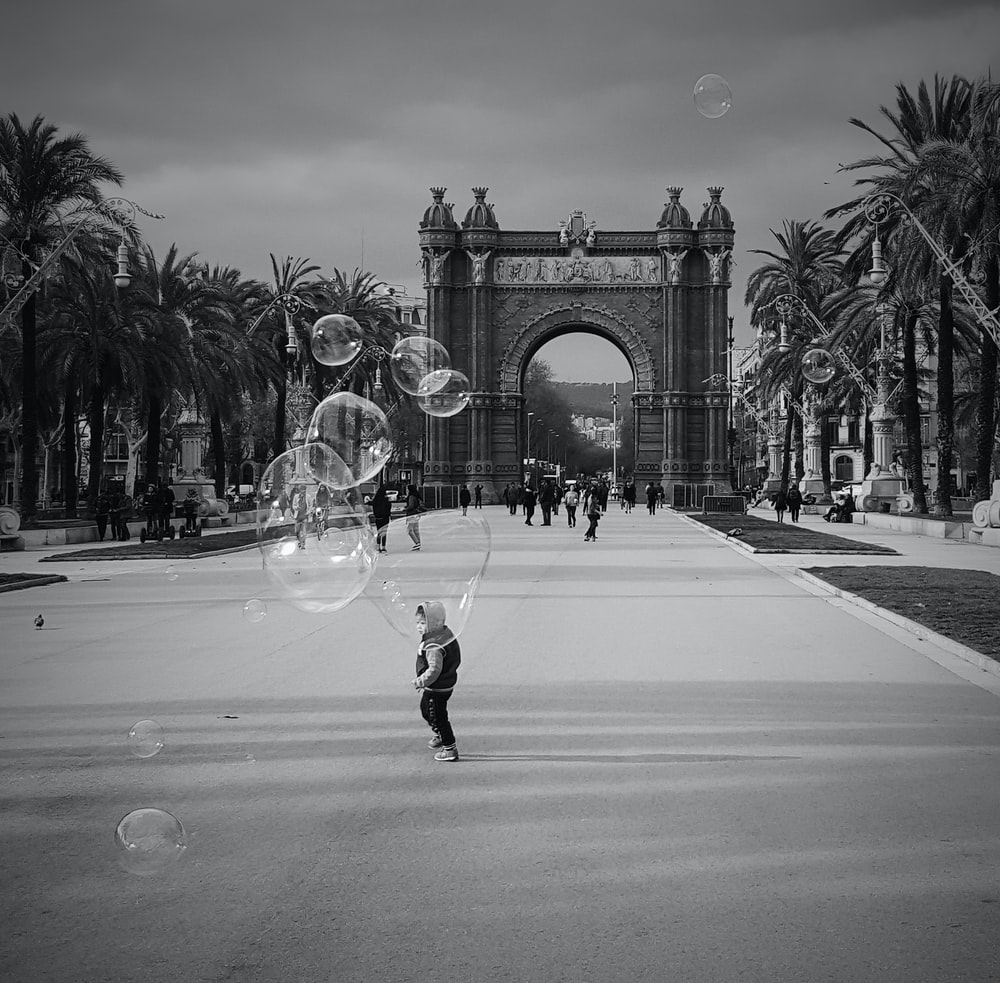 grayscale photo of girl playing bubbles on road