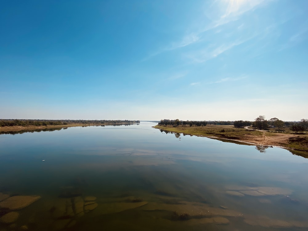 body of water near brown land under blue sky during daytime