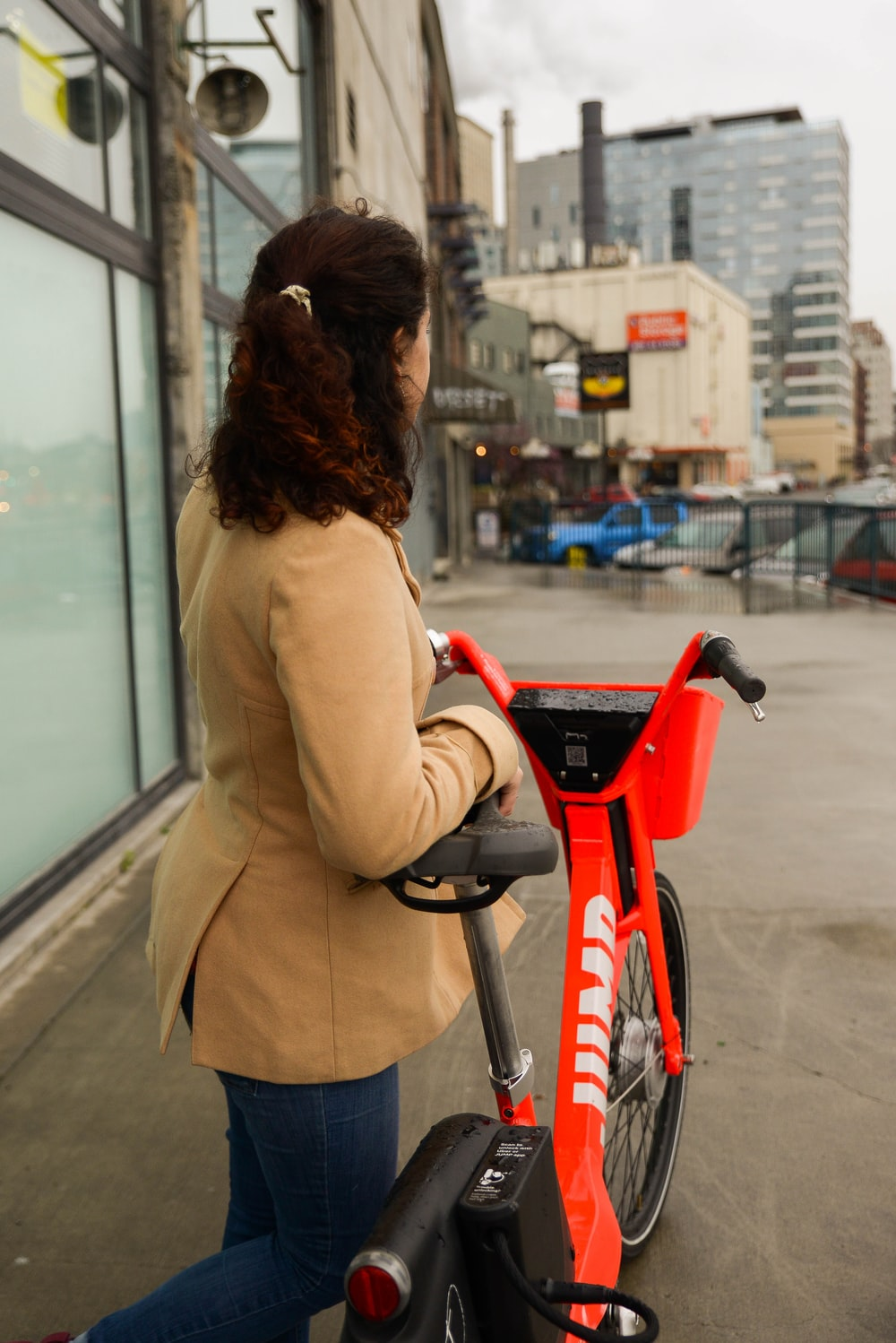 woman in beige coat riding red bicycle during daytime