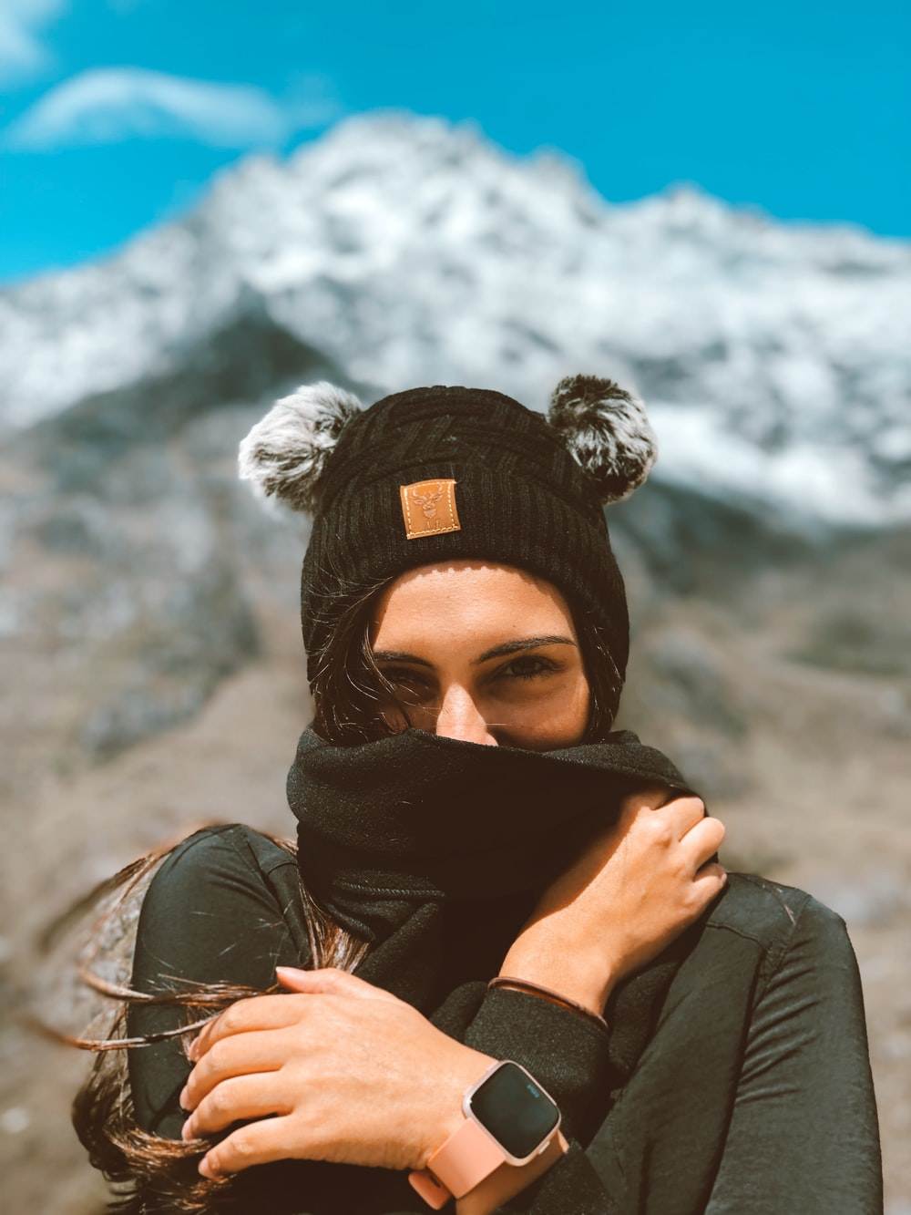 woman in black knit cap covering her face with black scarf
