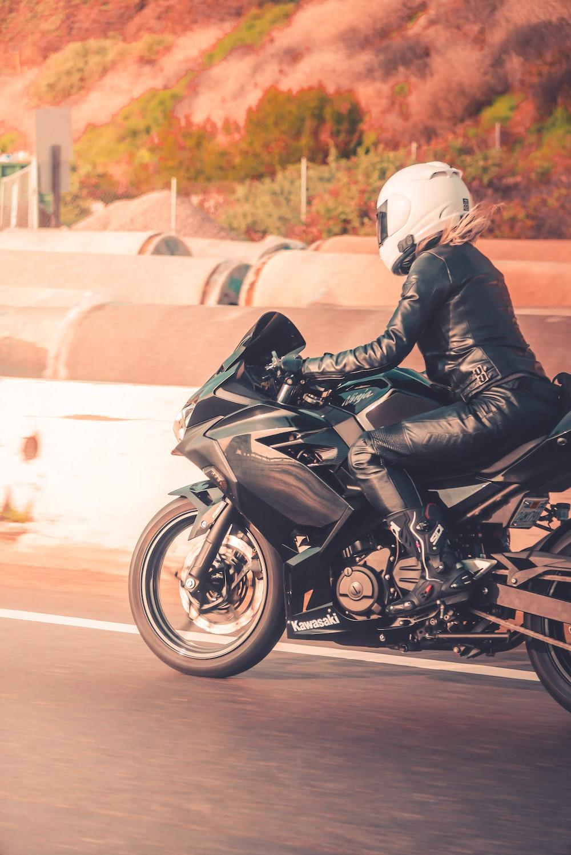 man in black leather jacket riding black sports bike on road during daytime