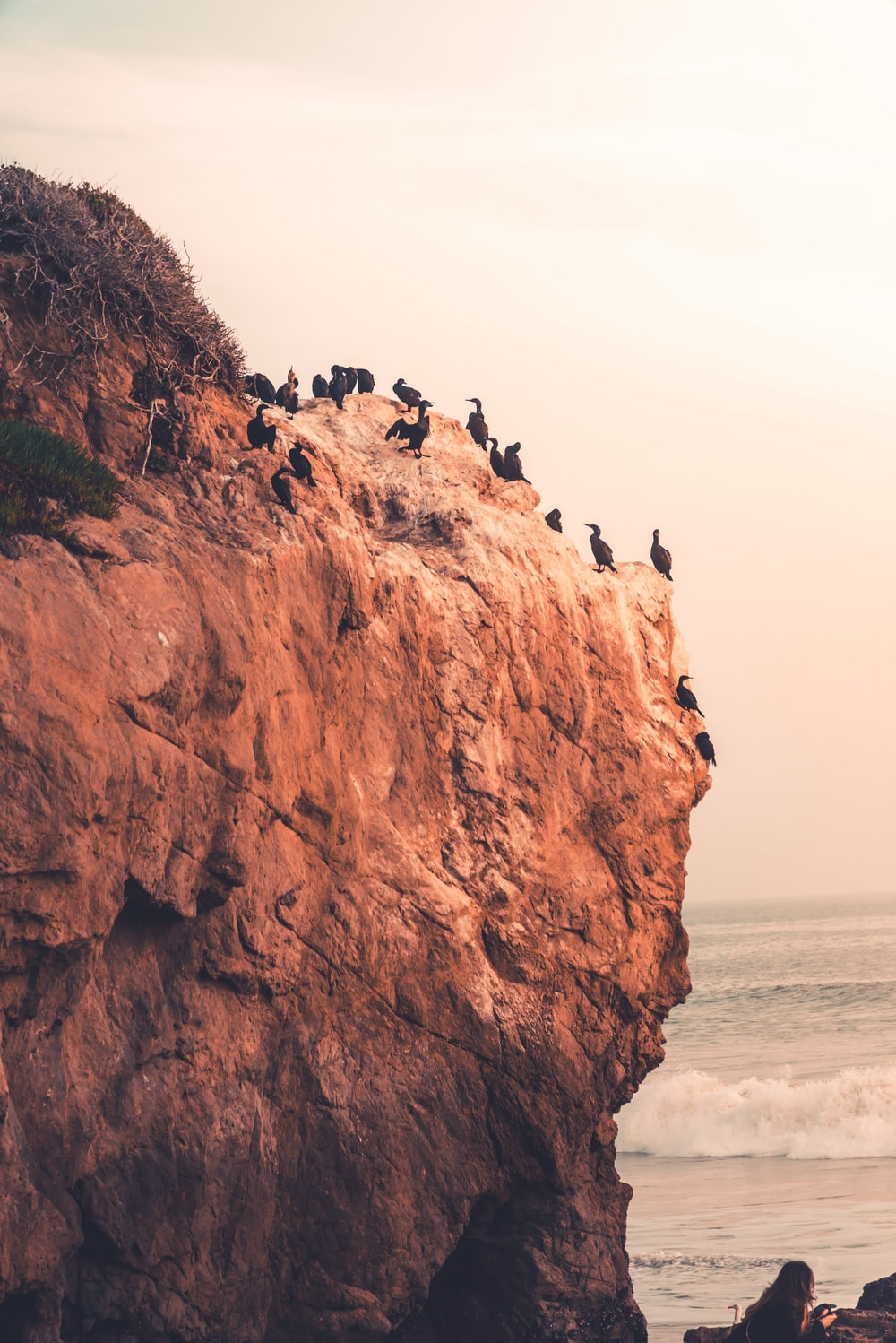 people standing on brown rock formation near sea during daytime