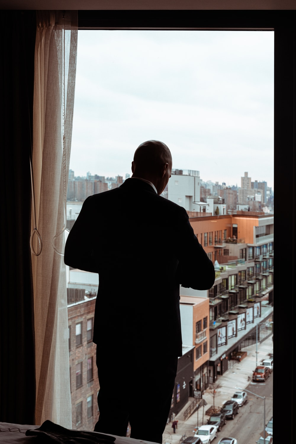 man in black dress shirt standing near window during daytime