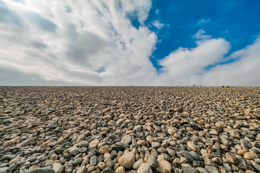 gray and black stones on brown sand under white clouds and blue sky during daytime