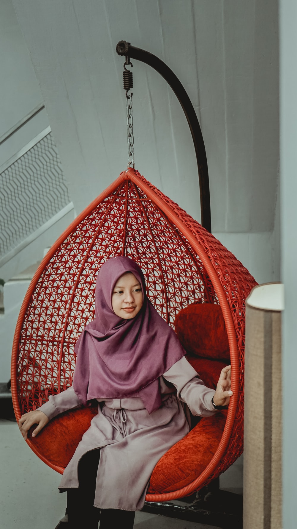 woman in purple hijab sitting on red chair