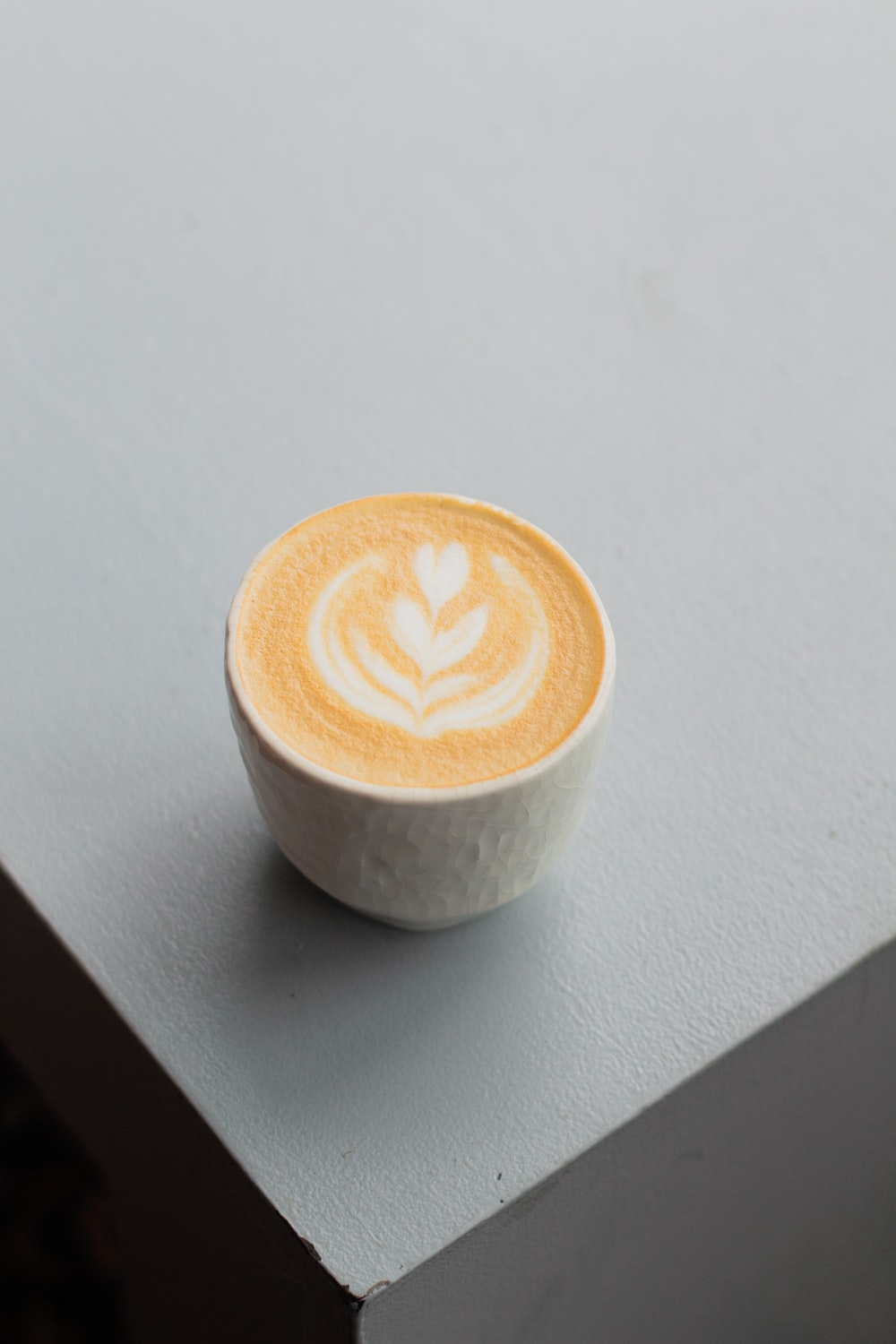 white ceramic cup with brown and white liquid