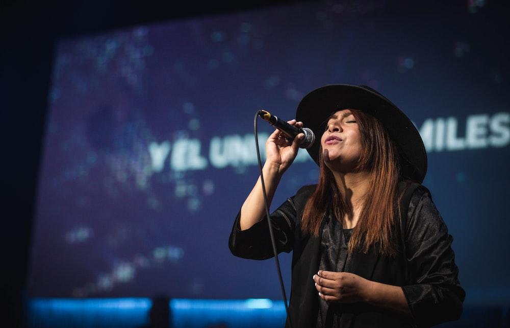 woman in black hat singing