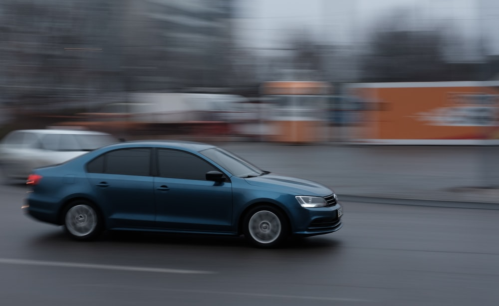 blue sedan on road during daytime